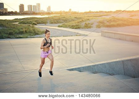 Fit young woman jogging up a flight of concrete stairs at the end of a rural road with a distant cityscape and rising glow of the sun in the background