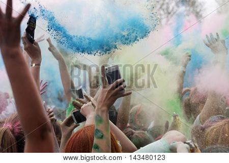 Closeup of happy hands throughing blue color powder in the air