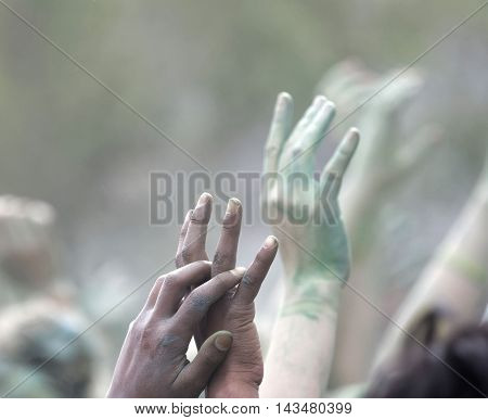 Closeup of raised hands with color powder