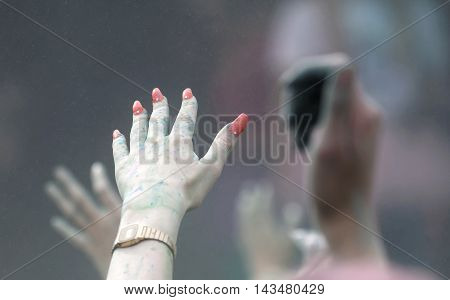 STOCKHOLM SWEDEN - MAY 22 2016: Closeup of hand with nail polish and color powder in the air in the Color Run Event in Sweden May 22 2016