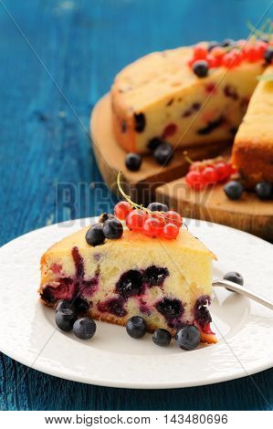 Slice of homemade oldfashioned cake with blueberries and red currants vertical