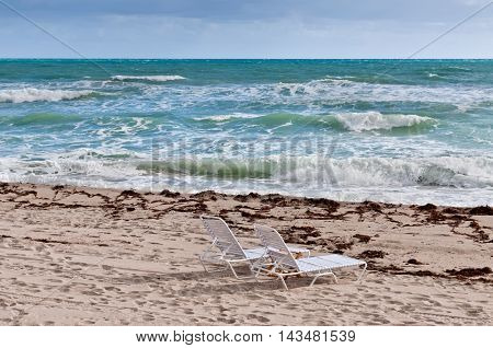 An empty beach chairs in front of a stormy sea