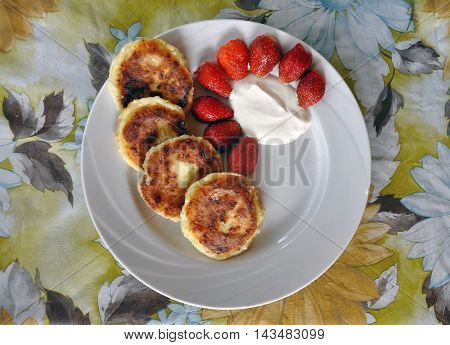 Country kitchen. Fried cheese pancakes with sour cream and strawberries on a white plate and a floral tablecloth. View from above.