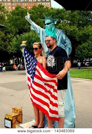 New York City - July 3 2007: Tourists posing with one of the many Statue of Liberty mime in Battery Park