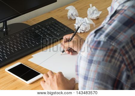 stressed man thinking and writting, crumber paper, smart phone on desk