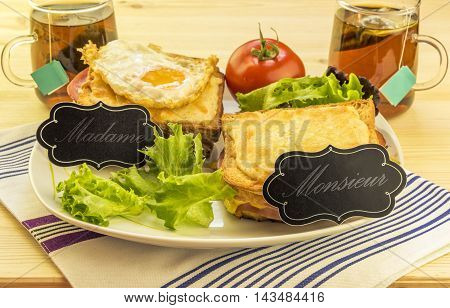 Special french sandwiches for men and women - Delicious meal with french sandwiches called croque madame and croque monsieur with labels for each one.