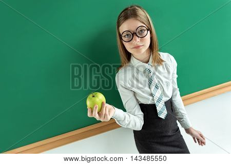 Attractive pupil in round glasses holding green apple. Creative concept with Back to school theme