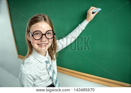 Portrait of cute schoolgirl in round glasses writing on blackboard in classroom. Education concept
