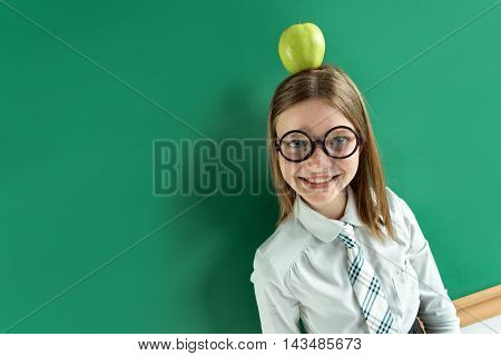 Smiling schoolgirl with an apple on her head. Photo of teen girl wearing glasses near blackboard. Creative concept with Back to school theme