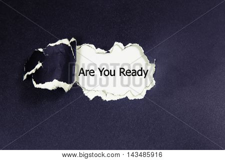 The question Are You Ready appearing behind torn black paper
