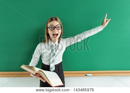 Cheerful enthusiastic pupil with open book pointing finger up. Photo of teen school girl wearing glasses creative concept with Back to school theme