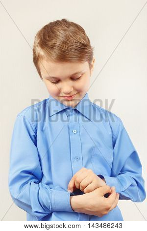 Little cute gentleman fastened the buttons on sleeve his bright shirt