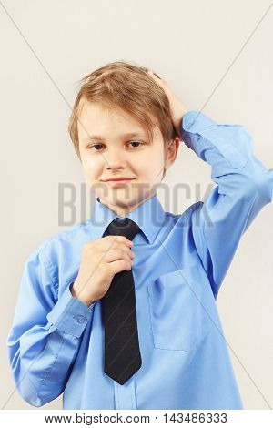 Little funny gentleman straighten his tie over bright shirt