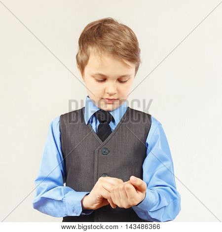 Little stylish boy fastened the buttons on sleeve his blue shirt