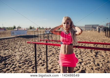 Beautiful fitness athlete woman resting after work out exercising on beach summer evening in sunny sunshine outdoor portrait