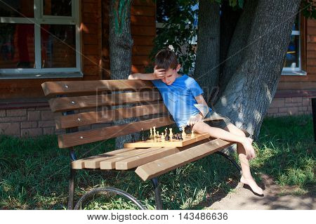 boy solves chess problems on the bench. boy learning to play chess on the book. playing with himself. the concept of education