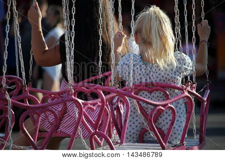 Young girls are sitting on a pink carousel in the amusement park on a sunny summer day