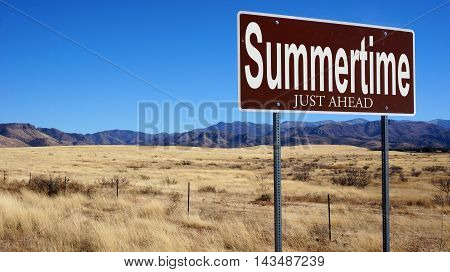 Summertime Just Ahead brown road sign with blue sky and wilderness