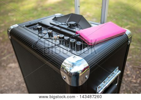 Mobile phone connected to portable PA sound system in the park