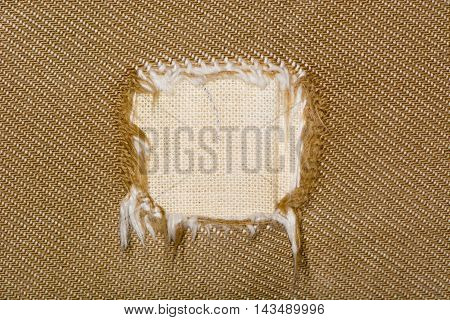 Square hole in fabric of sofa. Canvas like cotton material covering a brown settee unravelled into large square hole