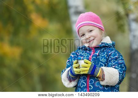 Fall outdoor head and shoulders portrait of little girl is holding steel thermos flask cup in hands