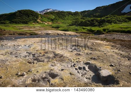 Boiling mud pots and hotsprings on the slopes of Mutnovsky volcano near the geothermal power plant, Kamchatka, Russia