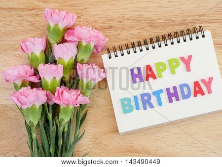 Word spell Happy Birthday on notebook and bouquet of sweet pink Carnation flower on wood background with top view