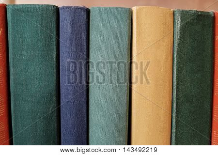 Horizontal stack of old books on a shelf