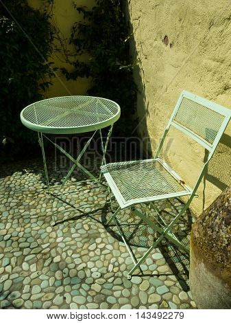 Rustic metal garden chair and table with grean cobble stone