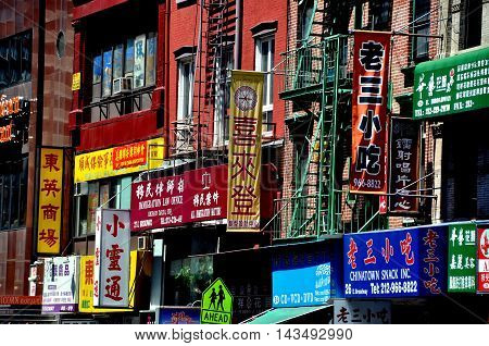 New York NY - May 2 2011: Shop and business signs mostly written in Chinese characters hang from tenenment buildings on East Broadway in Chinatown