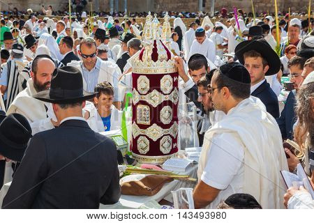 JERUSALEM, ISRAEL - OCTOBER 12, 2014: The area in front of Western Wall of Temple filled with people.  The Jews brought the Torah scroll for prayer