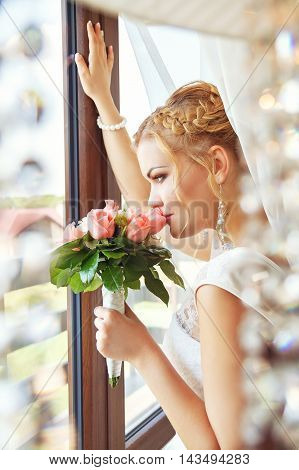 portrait of young dreaming bride in white dress with flowers near the window. Wedding portrait. Beautiful bride with flower bouquet standing near window. Bride waiting near the window for her groom. Portrait of bride in wedding makeup and hairstyle.