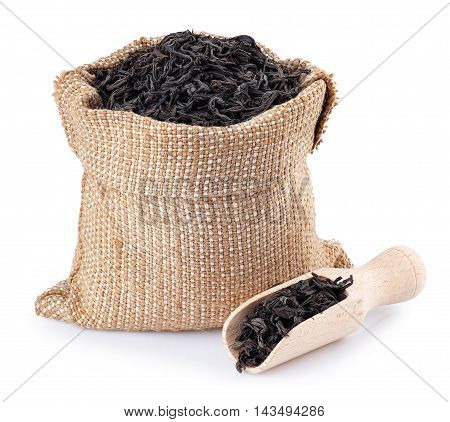 Black tea in burlap bag with wooden scoop near isolated on white background. Black tea. Dry leaves of tea in sack isolated on white