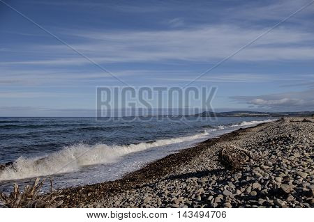 Waves crash on pebble beach on Scottish coastal village of Spey Bay with Moray Firth coastline in background