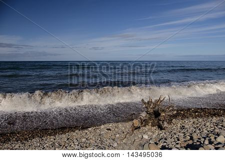 Waves crash on pebble beach at the coastal village of Spey Bay in Moray Scotland.