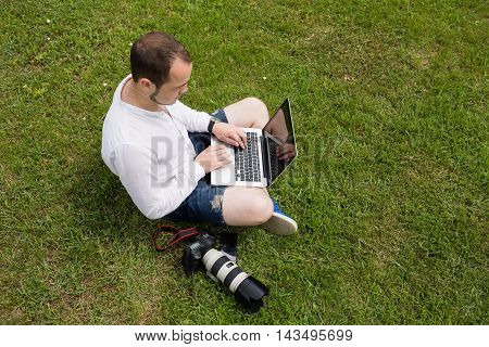 A photographer working on a laptop outdoors on green grass