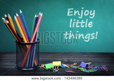 Enjoy little things text on green board and group of pencils