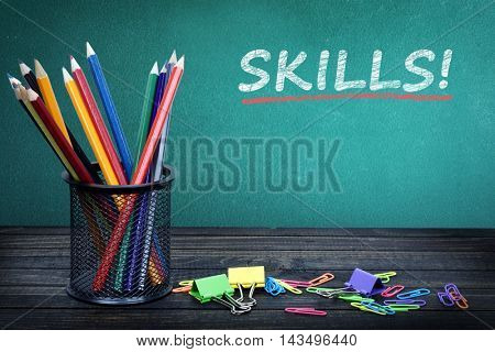 Skills text on green board and group of pencils