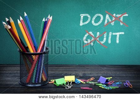 Don't quit text on green board and group of pencils