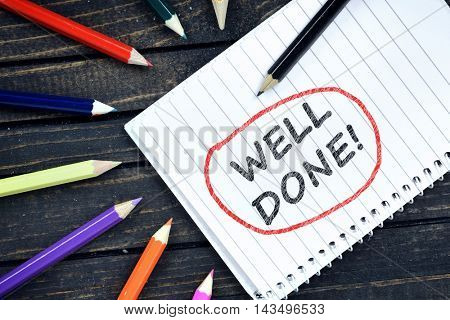 Well Done text on notepad and colorful pencils