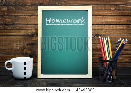 Homework text on school board and group of pencils