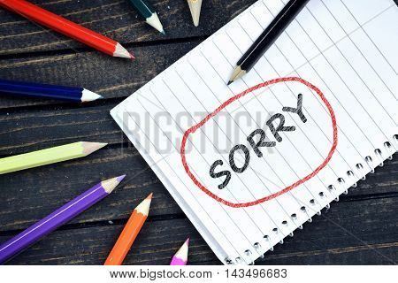 Sorry text on notepad and colorful pencils