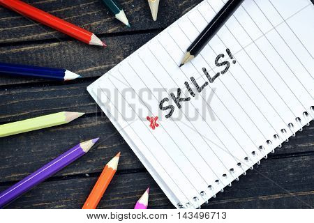 Skills text on notepad and colorful pencils