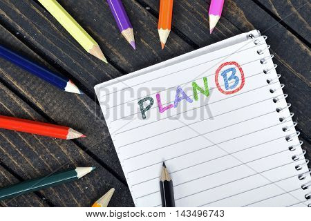 Plan B text on notepad and colorful pencils
