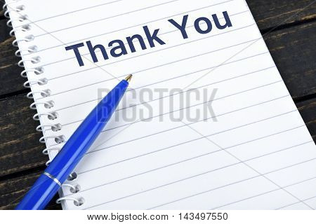 Thank You text on notepad and blue pen