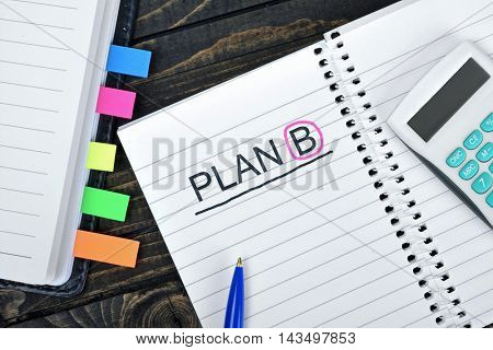 Plan B text on notepad and hand calculator