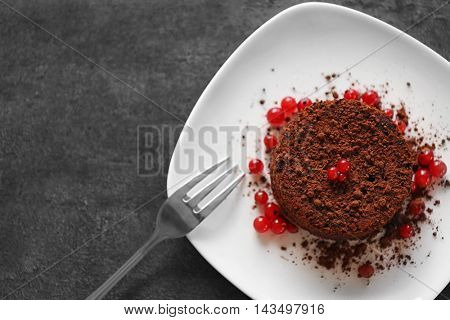 Tasty chocolate fondant with red currant on white plate, closeup