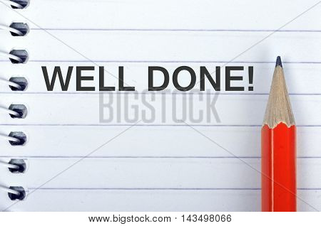 Well Done text on notepad and red pencil