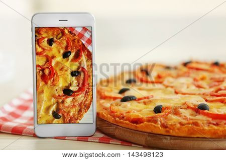 Pizza with smartphone on table. Food blog concept