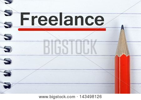 Freelance text on notepad and red pencil
